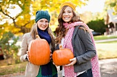 Two women holding orange pumpkins