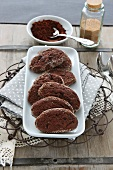 Chocolate cookies with cinnamon sugar round the edge, a small bowl of cocoa powder and a jar of cinnamon