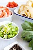 Verschiedene Zutaten: Lauch, schwarzer Pfeffer, Basilikum, gekochte geschälte Garnelen, Tomaten und Bandnudeln