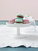 Macaroons on a cake stand with a domed glass cover in the background