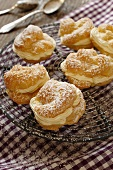 Profiteroles dusted with icing sugar, on a cooling rack