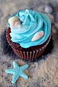 A chocolate cupcake with salted caramel and marine life decorations
