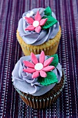 A chocolate cupcake and a lemon cupcake topped with purple icing