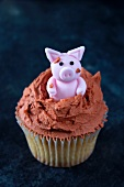 A cupcake topped with a piglet in mud