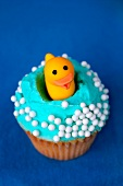 A cupcake topped with a rubber duck