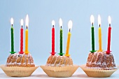 Three Bundt cakes with lit candles, for a birthday