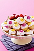 Lots of mini cupcakes decorated with sugar flowers, on a cake stand