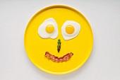 Smiley mit Spiegeleiaugen, Spargelnase und lächelndem Baconmund