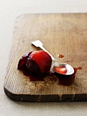 A poached plum with some juice on a chopping board