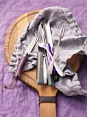 Knives, a fork and a serving fork lying on a cloth on a wooden board