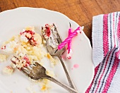 The remains of a slice of birthday cake with candles
