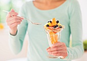 A woman holding a sundae glass of fruit salad