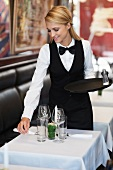 A waitress laying the table in a restaurant