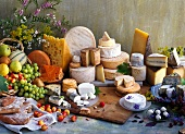 A still life of cheese with fruit, bread and flowers
