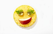 Smiling face made from pineapple, kiwi and apple