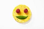 Lächelndes Obstgesicht aus Ananas, Himbeeren und Blatt