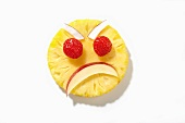 An angry face made from pineapple, apple, raspberries and coconut