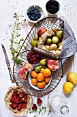 A still life of a wire basket with fresh summer fruits