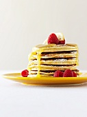 A Stack of Pancakes with Powdered Sugar, Honey and Raspberries