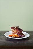 Pork Shank with Root Vegetables and Grilled Onion on a White Plate