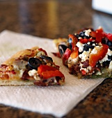 Olive, Red Pepper and Feta Pizza Slices on a Paper Napkin