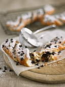 A puff pastry twist with chocolate chips and icing sugar