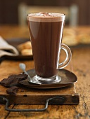 A glass of hot chocolate and pieces of chocolate