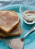 Toast with cinnamon sugar on a blue plate, with cinnamon sugar mixture in a glass and on a spoon