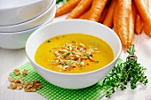 Celery and carrot soup garnished with fried celery, bell pepper, walnuts and thyme; selective focus