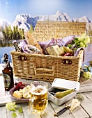 A table with a light meal and a picnic basket against a mountain view