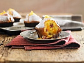 An orange and cranberry muffin with a bite missing
