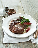 Beef steak with salad leaves, mustard, salt and pepper