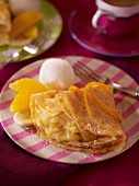 A pancake with stewed banana, orange pieces and vanilla ice cream