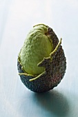 An avocado, partly peeled