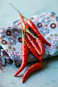 Fresh red chillies on a floral-patterned cloth