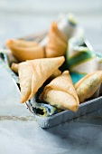 Samosas on a cloth in an aluminium dish