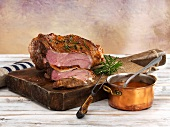 Leg of lamb, cooked pink, on a wooden board