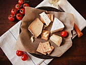 Assorted Cheeses and Crackers in a Paper Lines Bowl with Fresh Tomatoes