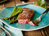 Strip Steak with a Piece Pierced on a Fork; Served with Asparagus on a Blue Plate