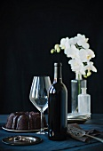 Wine Bottle, Wine Glass and a Whole Chocolate Bundt Cake; White Flowers in the Background