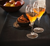 Two Glasses of Dessert Wine on a Table; Bowl of Fruit in the Background