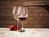Rotwein aus Dekanter in ein Glas gießen, leeres Weinglas und Granatapfel