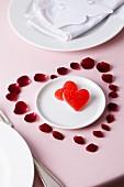 Rosenblütenblätter in Herzform dekoriert um Teller mit Süßigkeiten
