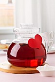 A tea pot decorated with a paper heart