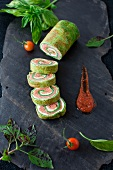 Spinach and Basil Smoked Salmon Roll; Sliced with Sauce on a Piece of Slate