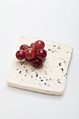 A slice of blue cheese and red grapes