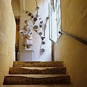 Steinskulptur einer historischen Frauenfigur und dekorative Laubranken am oberen Absatz eines steinernen, alten Treppenaufgangs