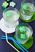 Clover leaf-shaped ice cubes in drinking glasses