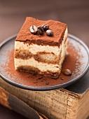 Ein Stück Tiramisu mit Mokkabohnen und Kakaopulver