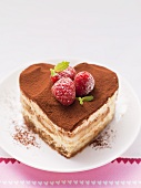 A heart-shaped tiramisu with raspberries